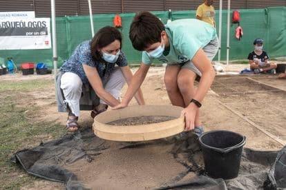 Una madre, María García, arqueóloga que participó en las primeras excavaciones, ayuda a su hijo Aarón a cribar la tierra por si quedaran restos que han pasado inadvertidos.